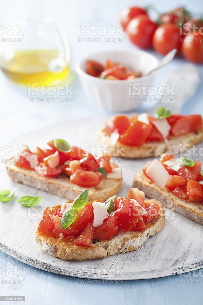 Italian bruschetta with tomatoes, parmesan, garlic and olive oil stock photo