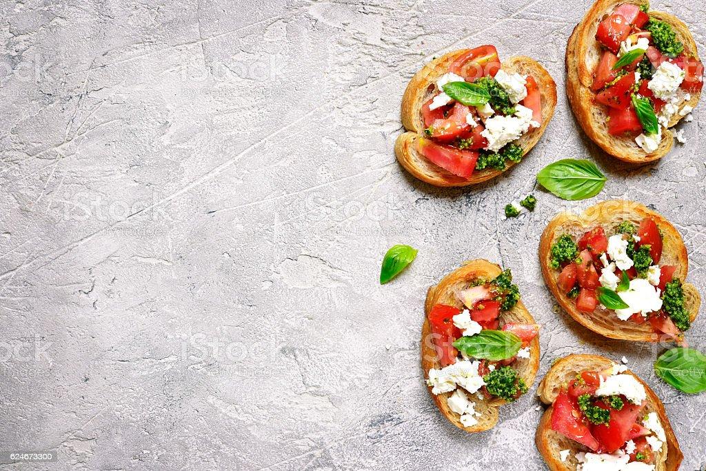 Italian bruschetta with tomatoes,feta and basil pesto on . stock photo