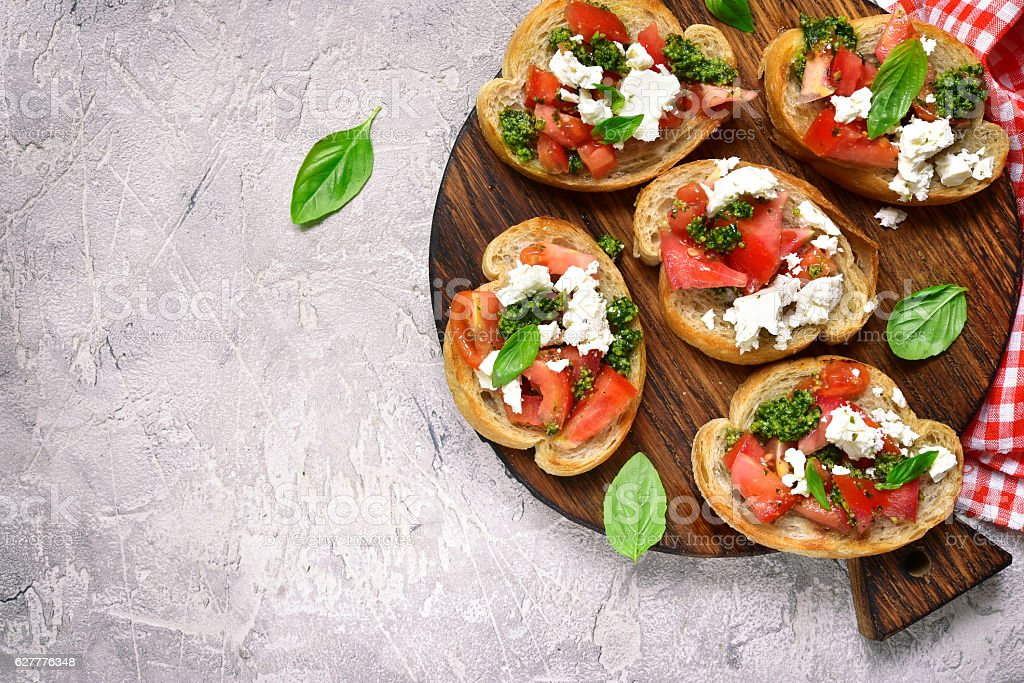 Italian bruschetta with tomatoes,feta and basil pesto. stock photo