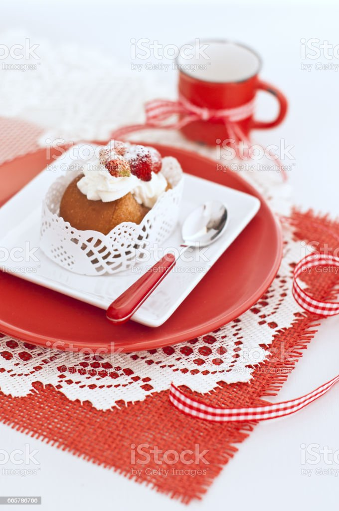Italian cake baba with a cream and strawberries in white and red plates, red cup with ribbon on napkin on wooden board stock photo
