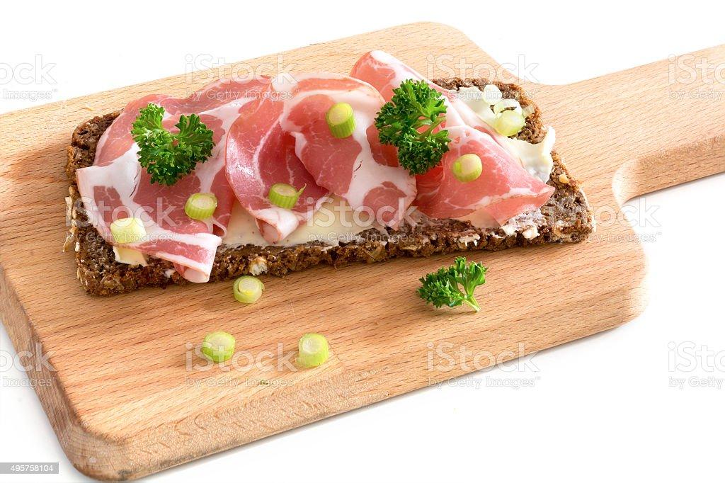 Italian capicola ham on bread on a wooden board stock photo