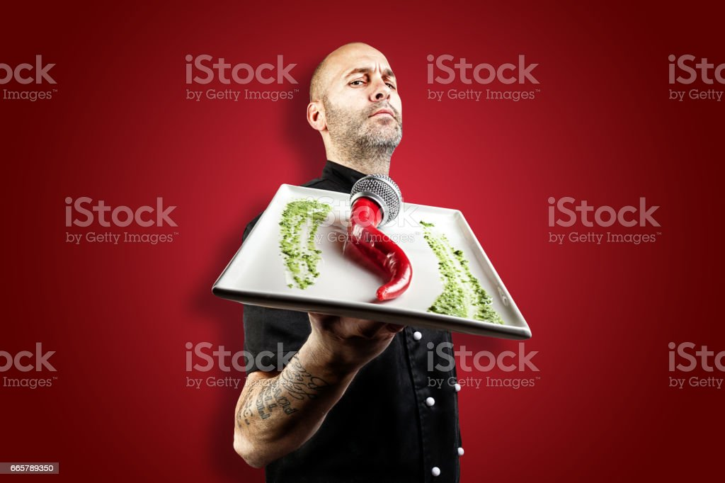 Italian Chef with plate in hand with microphone chili stock photo