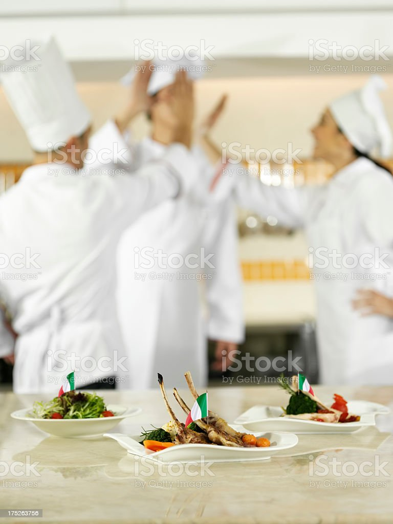 Italian Chefs High-Fiving In Kitchen royalty-free stock photo