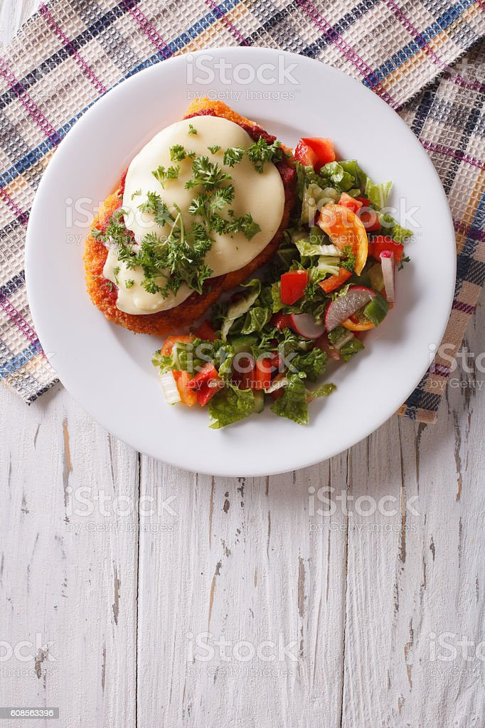 Italian chicken Parmigiana and salad. Vertical top view stock photo