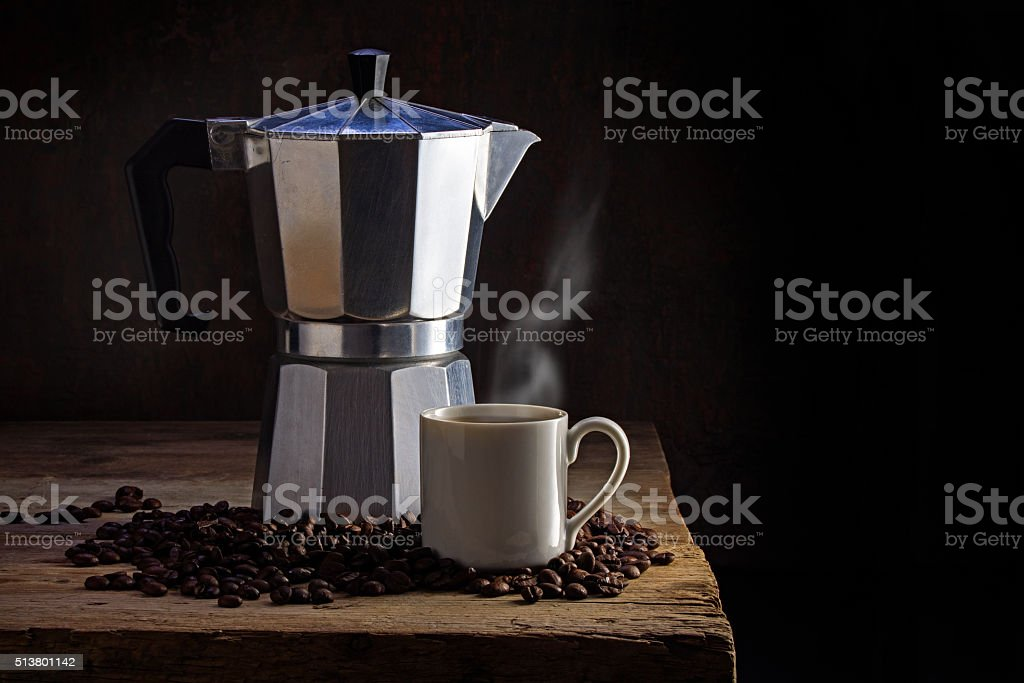 Italian coffee maker, cup of steaming coffee and whole beans stock photo