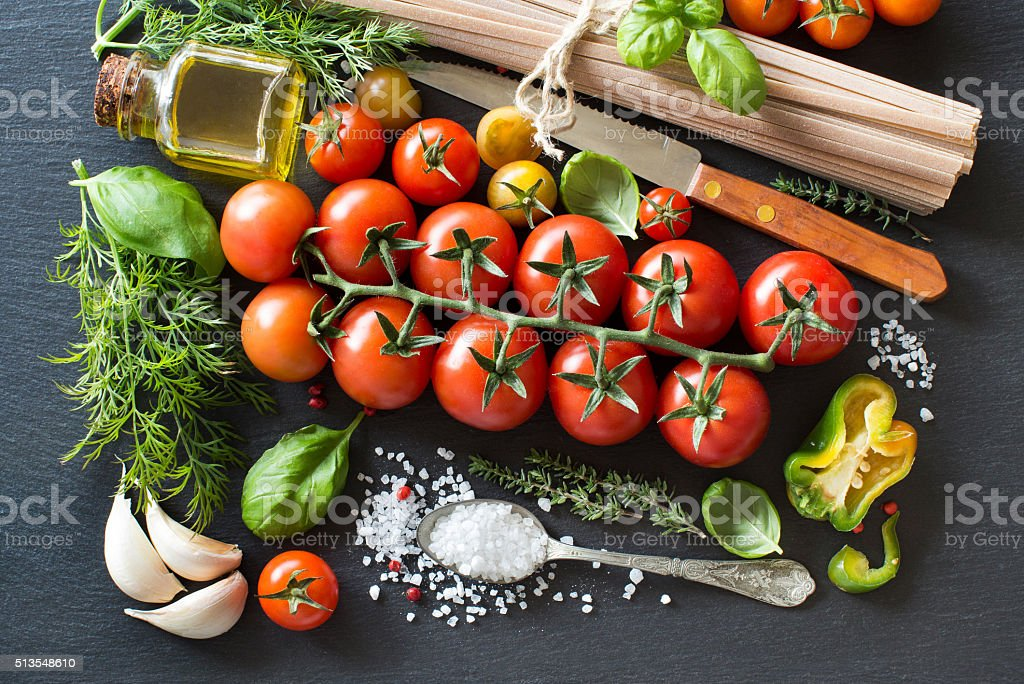 Italian cooking ingridients : cherry tomatoes, herbs, pasta and stock photo