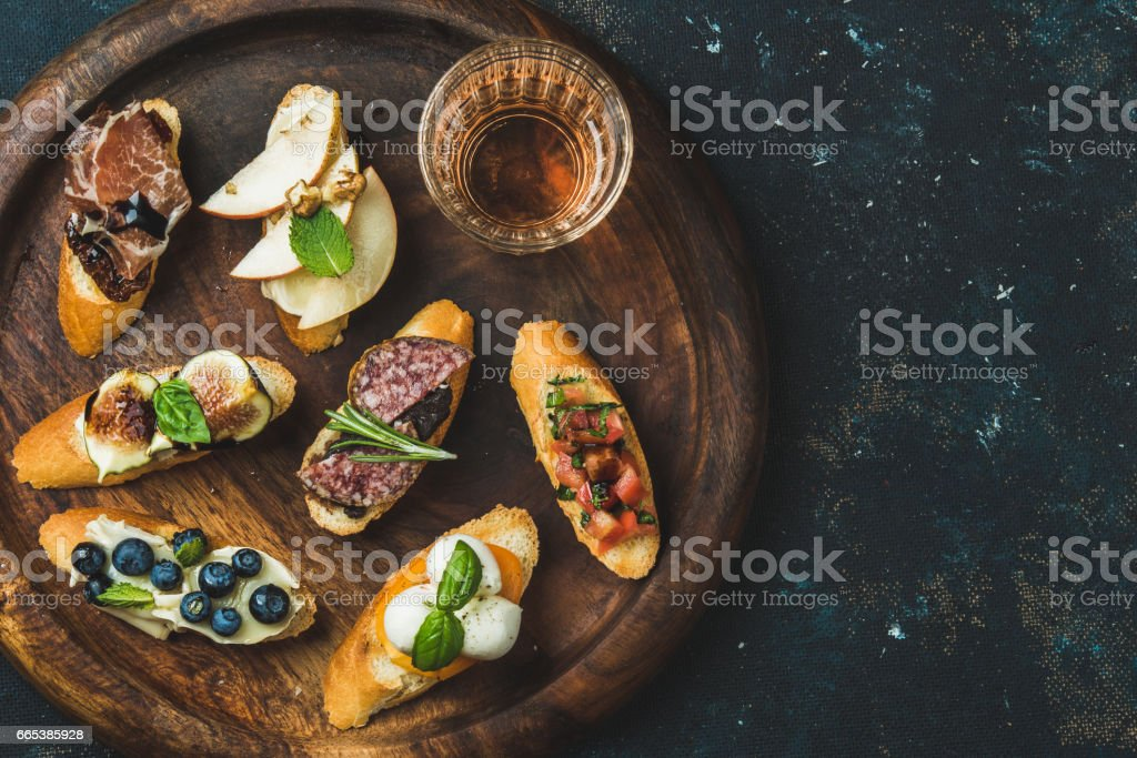 Italian crostini and glass of wine in wooden tray stock photo