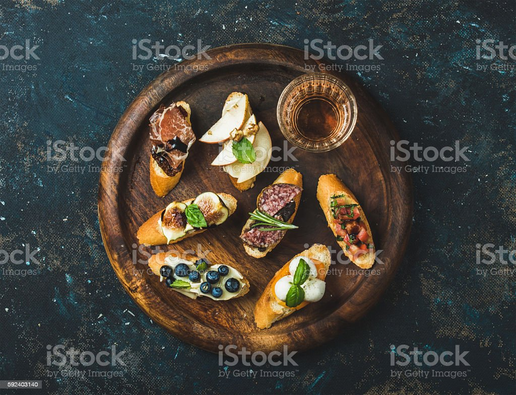 Italian crostini and glass of wine on round serving tray stock photo