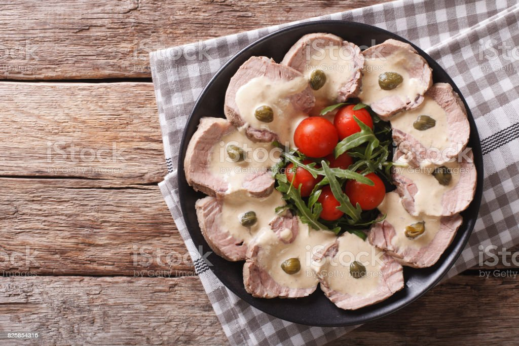 Italian cuisine: Vitello tonnato with capers, arugula, tomatoes close-up. Horizontal top view stock photo