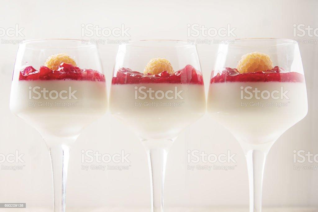 Italian dessert. Vanilla panna cotta with raspberry jam. Stone background. stock photo