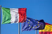 Italian European and Spanish Flags on Blue Sky