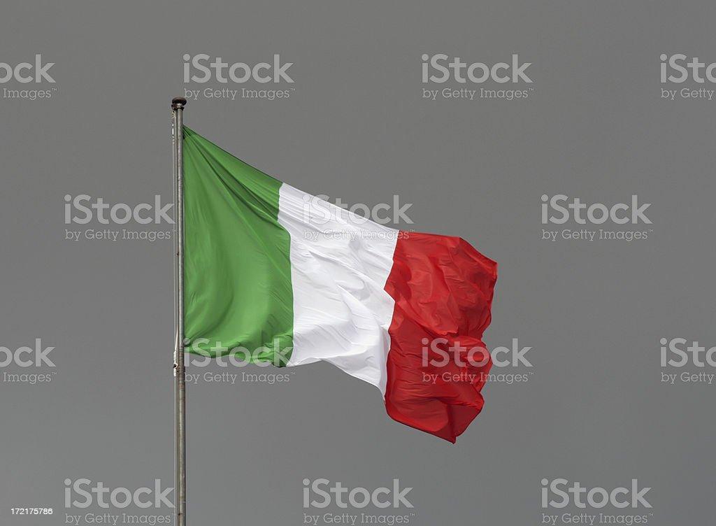 Italian flag against a grey sky, Italy stock photo