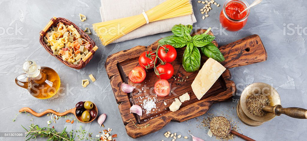 Italian food background Tomatoes, basil, spaghetti, parmesan, olive oil, garlic stock photo