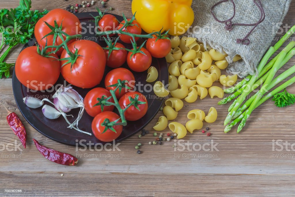 Italian food cooking ingredients on wooden background, uncooked pasta and vegetables, different tomatoes, garlic, asparagus, bell pepper. Top view, copy space stock photo