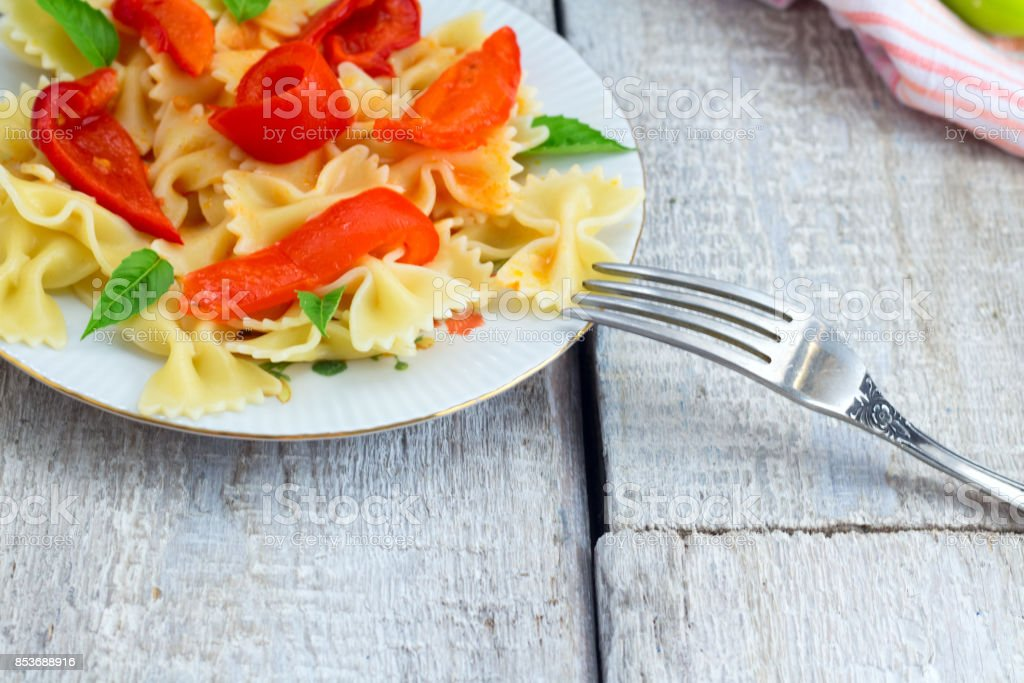 Italian food. Pasta fusilli with tomato sauce, peppers and basil on wooden background stock photo