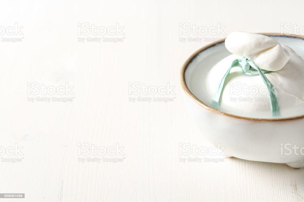 Italian fresh burrata cheese in a ceramic bowl. Light white back stock photo