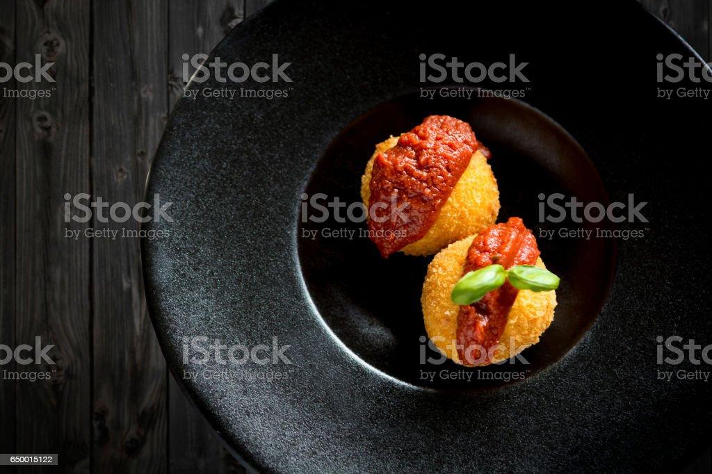 Italian fried rice balls tomato sauce black plate stock photo