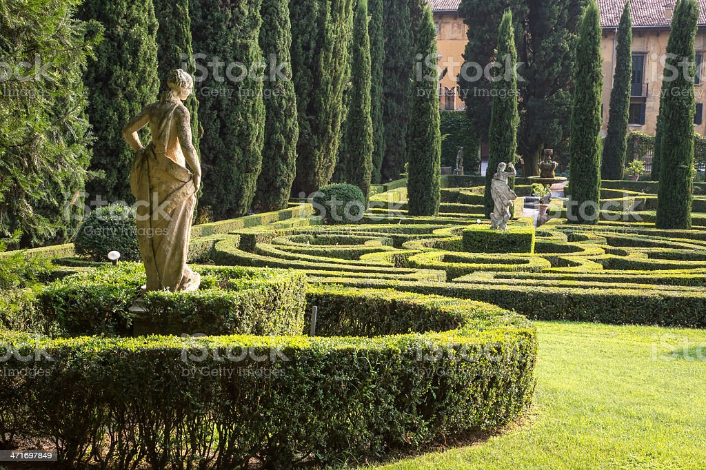 Italian garden with statues, maze and cypress trees stock photo