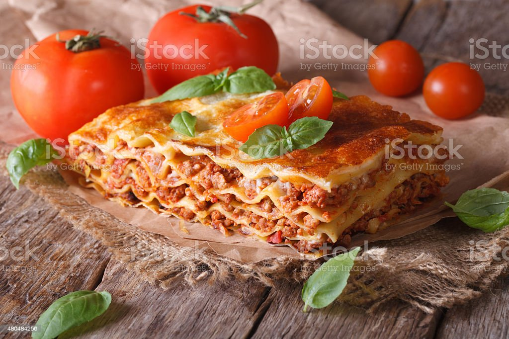 Italian lasagna with basil close-up on paper, horizontal rustic stock photo