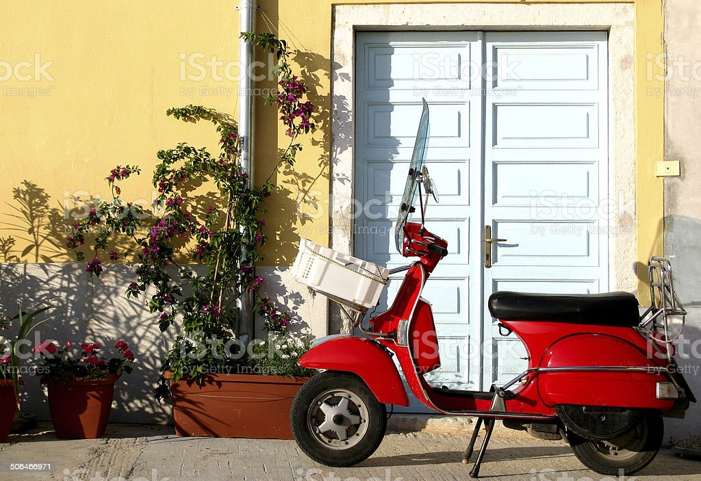 italian old style red scooter near a door royalty-free stock photo