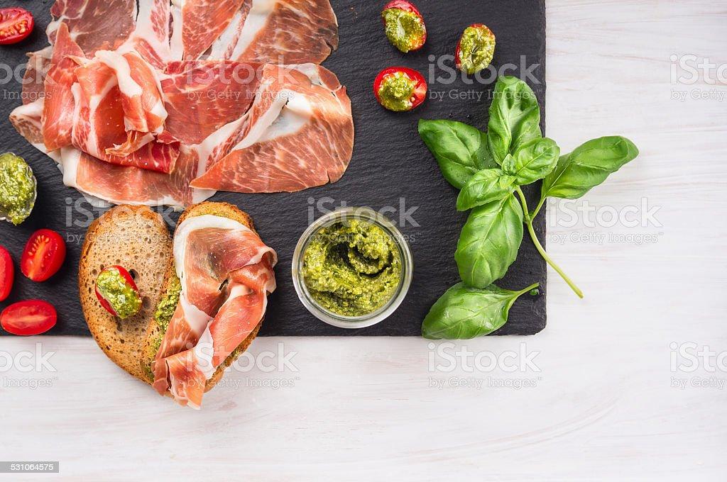 italian parma ham with basil pesto, tomatoes and bread stock photo