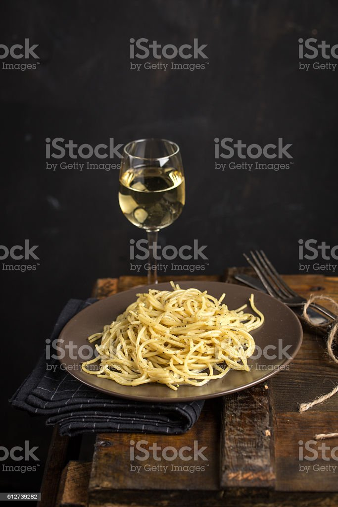 Italian pasta and glass of white wine stock photo