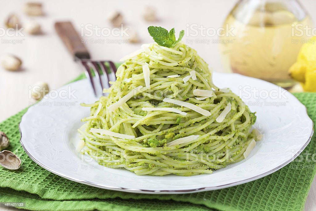 Italian pasta spaghetti with pesto green peas, mint, pistachios stock photo
