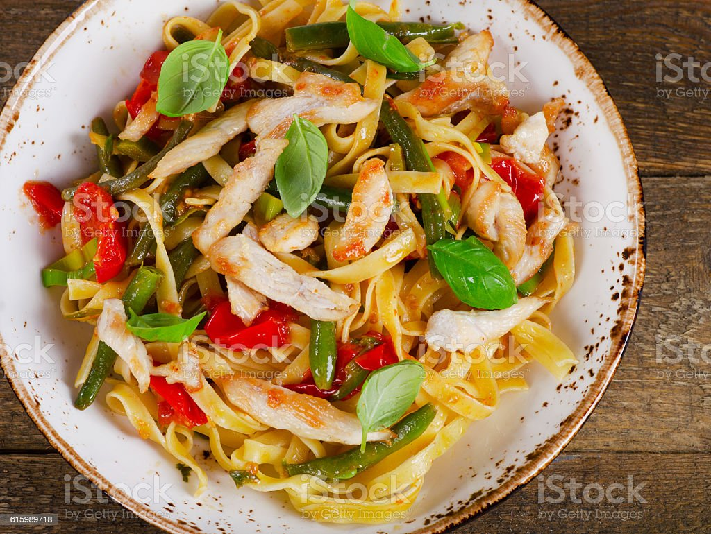 Italian Pasta with chicken and vegetables on  wooden table. stock photo