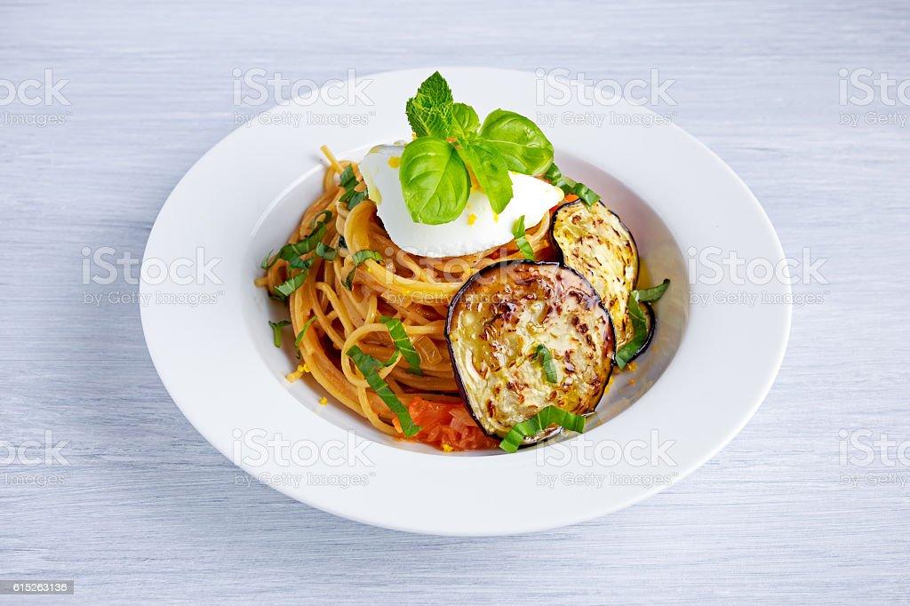 Italian Pasta with eggplants, tomato, ricotta cheese and basil stock photo