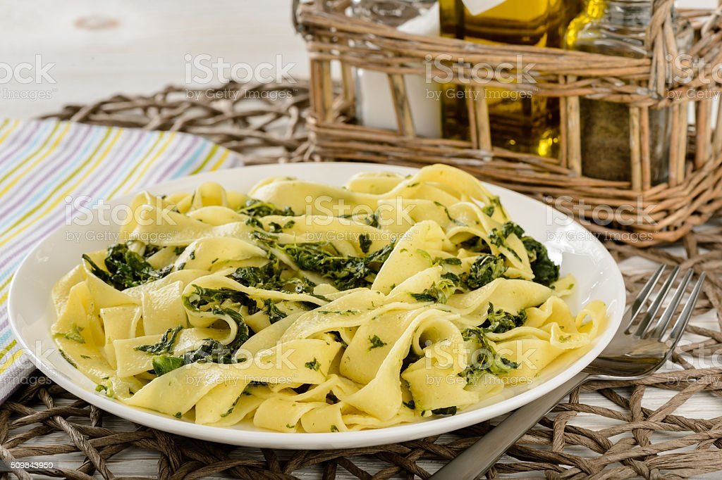 Italian pasta with spinach and sour creme on wooden table. stock photo