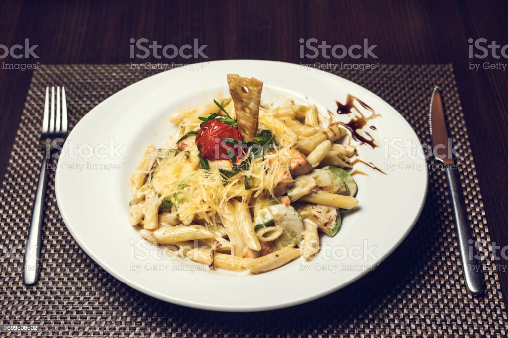 Italian penne pasta with vegetables and grade cheese. stock photo