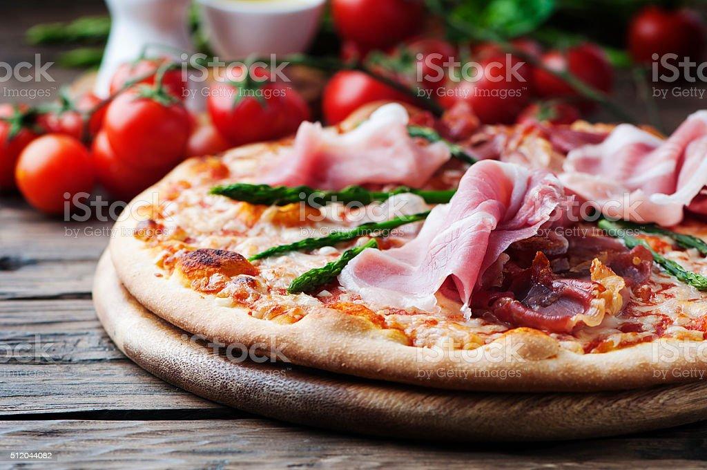 Italian pizza with ham and asparagus stock photo