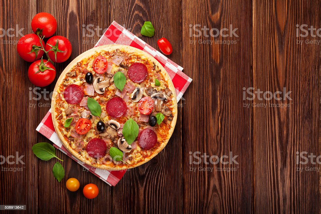 Italian pizza with pepperoni, tomatoes, olives and basil stock photo