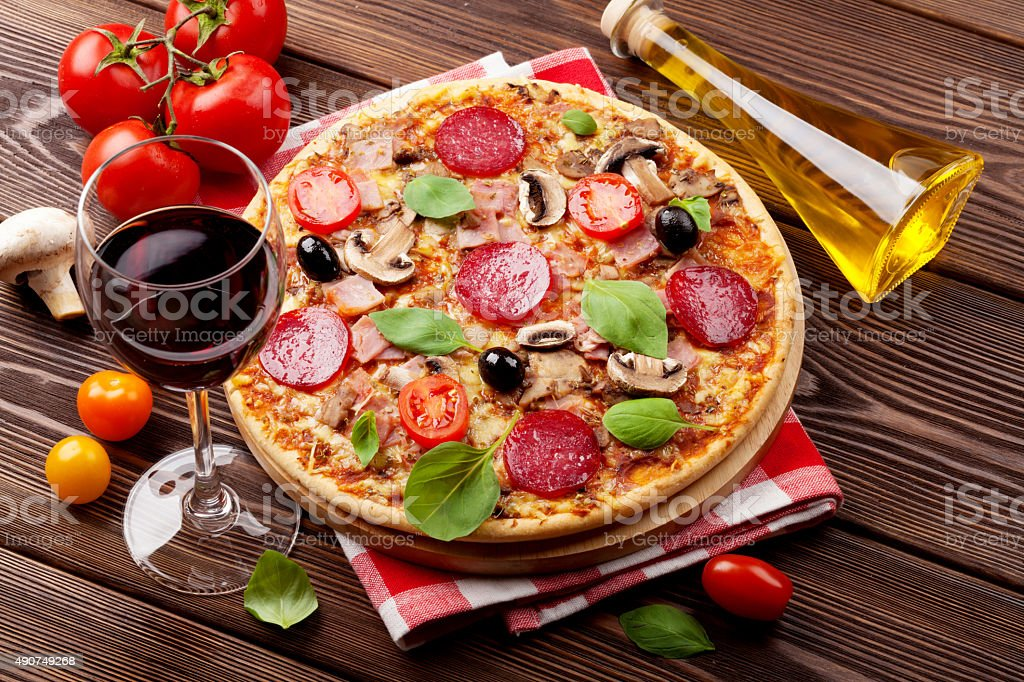 Italian pizza with pepperoni, tomatoes, olives, basil and red wi stock photo