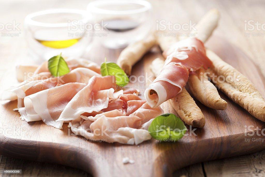 italian prosciutto ham grissini bread sticks olive oil stock photo