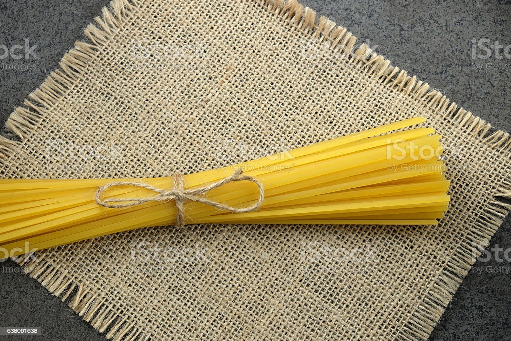 Italian raw bavetti tied with twine on burlap cloth and stock photo