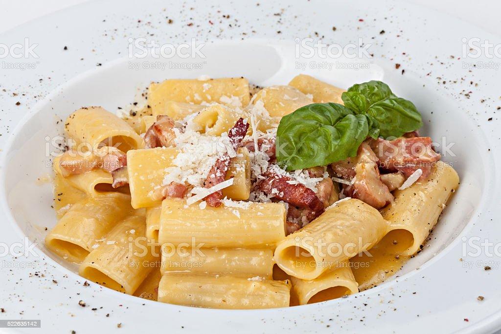 Italian rigatoni pasta with prosciutto, parmesan cheese and leaf stock photo