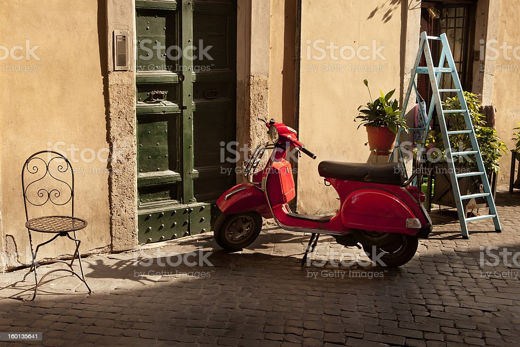 Italian sunny scene, red scooter in front of home door stock photo