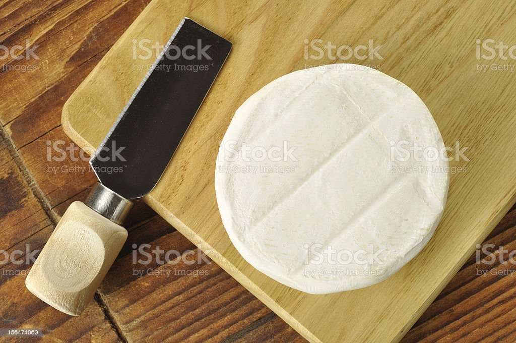 Italian tomino cheese on a wooden chopping board stock photo