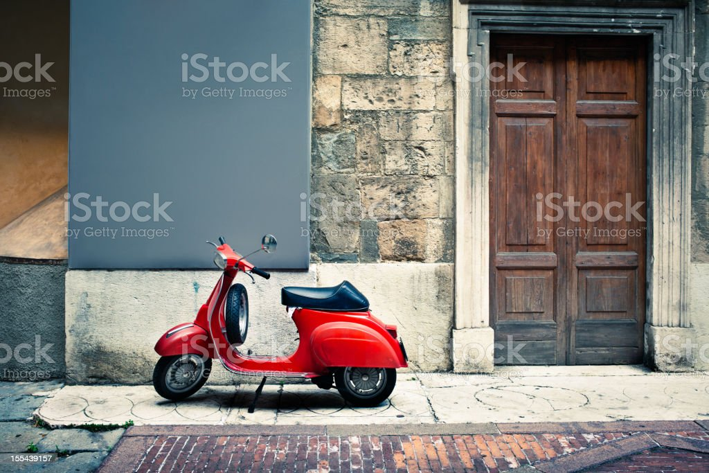 Italian vintage red scooter in front of a house stock photo