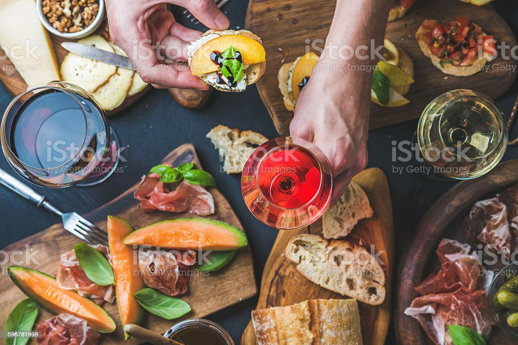 Italian wine snack variety, man's hands holding glass of stock photo