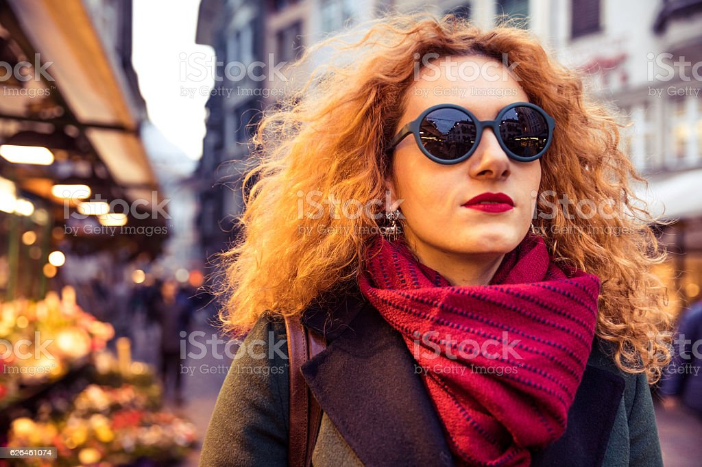 Italian woman wearing sunglasses at late afternoon in the city stock photo