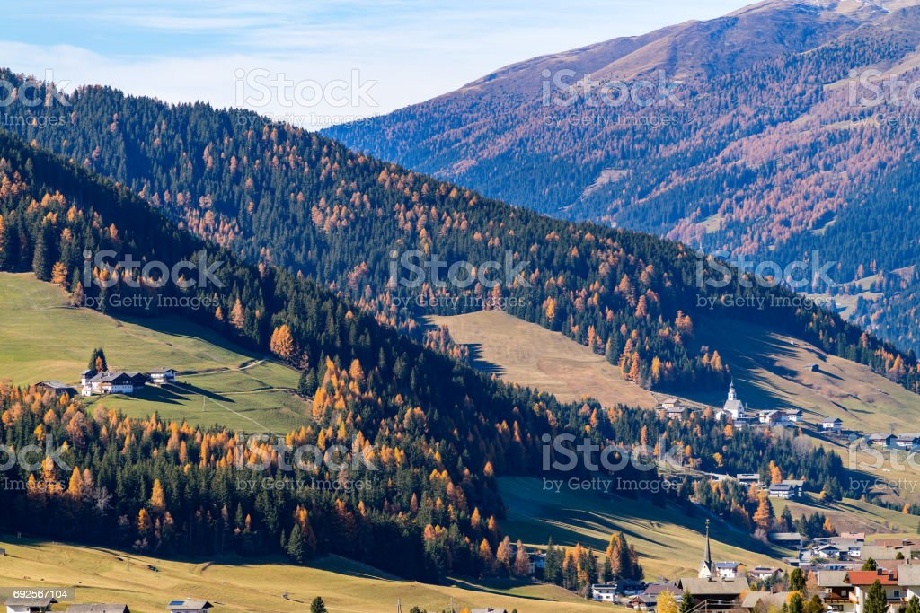 Italy. Dolomites. Autumn landscape with bright colors, house and larch trees in the sunlight. stock photo