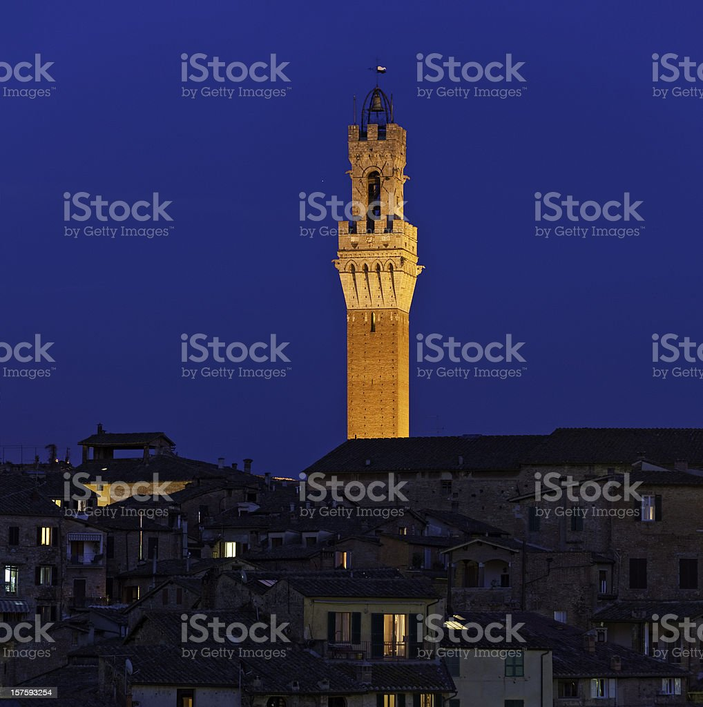 Italy Siena Torre del Mangia illuminated windows villas dusk Tuscany stock photo