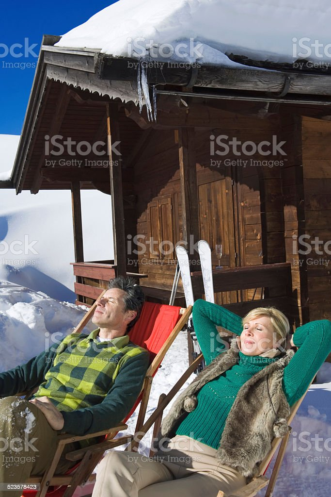 Italy, South Tyrol, Couple resting in chairs by log cabin stock photo