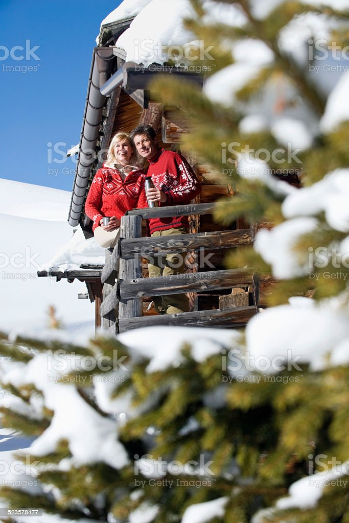 Italy, South Tyrol, Couple standing on deck of log cabin stock photo