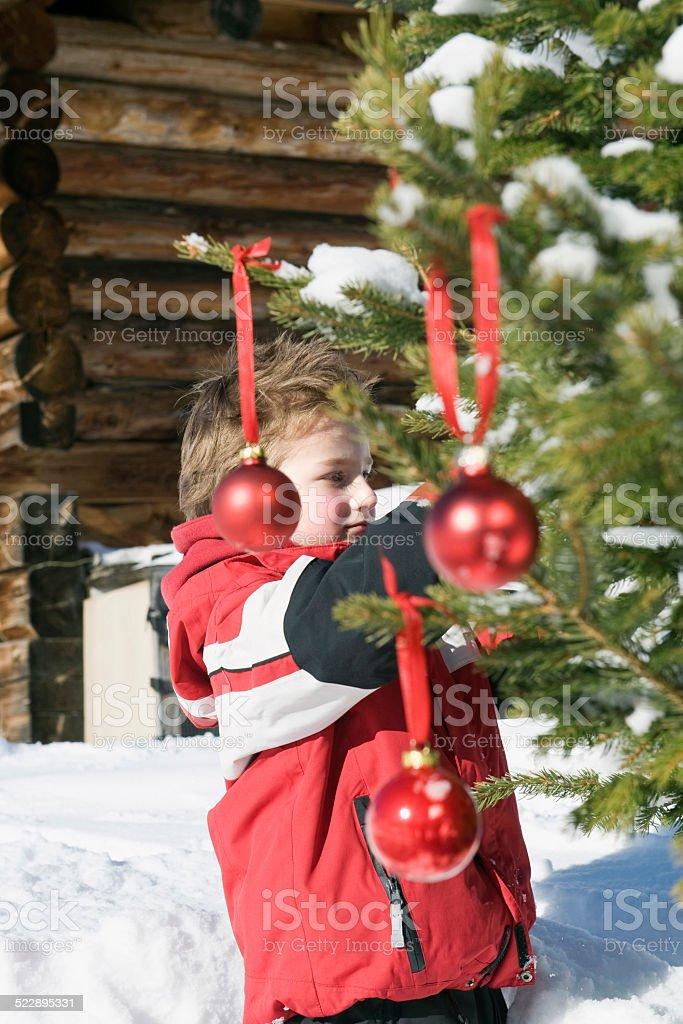 Italy, South Tyrol, Seiseralm, Boy decorating Christmas tree in snow stock photo