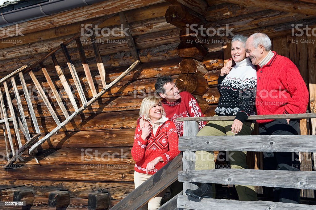 Italy, South Tyrol, Seiseralm, Log Cabin, Couple standing on balcony stock photo