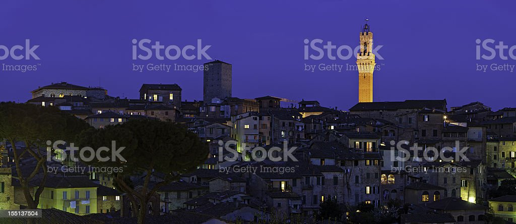 Italy Torre del Mangia illuminated rooftop panorama Siena Tuscany stock photo