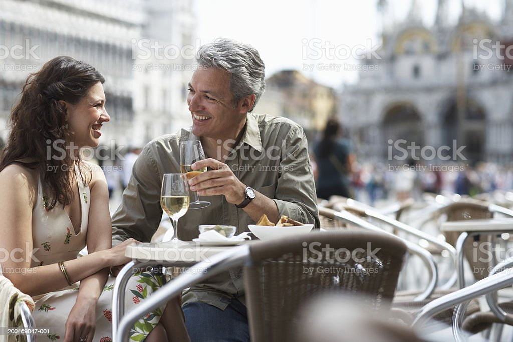 Italy, Venice, couple drinking champagne at cafe table, outdoors stock photo